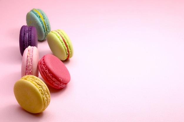 Maccherone o macaron variopinto del dolce su fondo rosa dalla vista superiore, biscotti variopinti