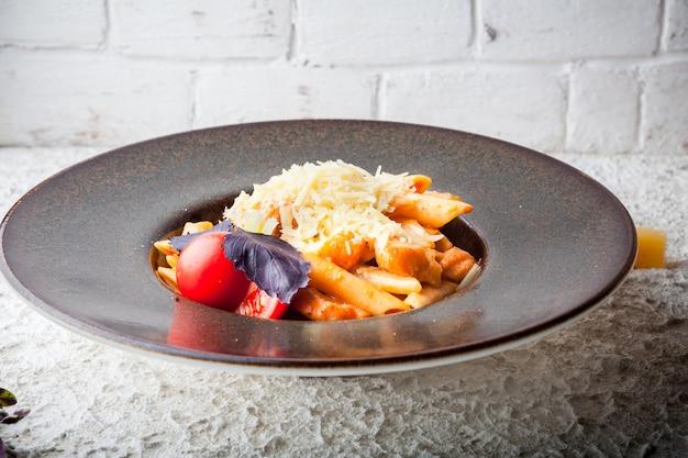 Maccheroni con formaggio e pomodori e basilico viola nel piatto rotondo