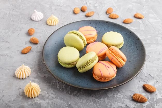 Maccheroni e maccheroni arancio e verdi dei maccheroni sul piatto ceramico blu su un fondo concreto grigio. vista laterale.