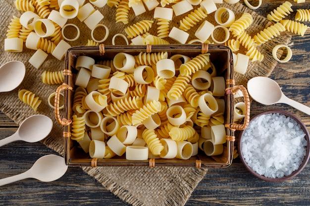 Maccheroni in un vassoio con cucchiai, sale vista dall'alto su una tela di sacco e fondo in legno