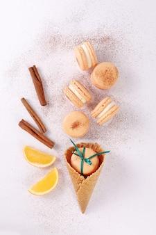 Maccheroni o maccheroni francesi colorati del dessert su un fondo bianco sotto forma di gelato con il cono della cialda, l'arancia e la cannella. approccio creativo.