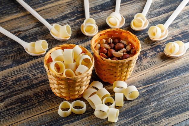 Maccheroni pasta in ciotole e cucchiai con pistacchi e nocciole vista dall'alto su uno sfondo di legno scuro