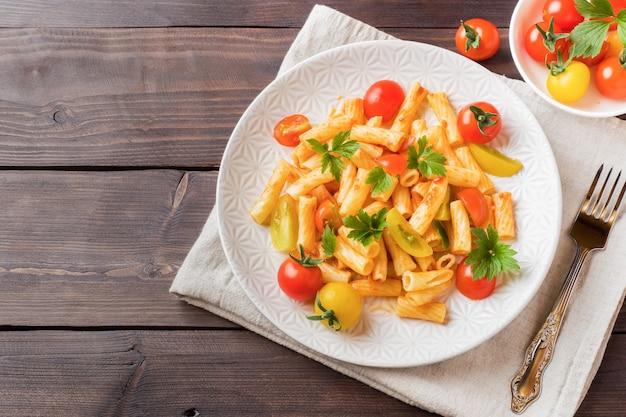 Maccheroni, pasta in salsa di pomodoro e formaggio in un piatto su un tavolo di legno