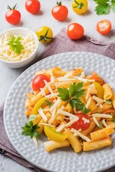 Maccheroni, pasta in salsa di pomodoro e formaggio in un piatto su un tavolo di legno.