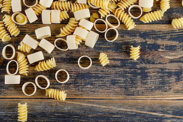 Maccheroni pasta su uno sfondo di legno. disteso. spazio per il testo