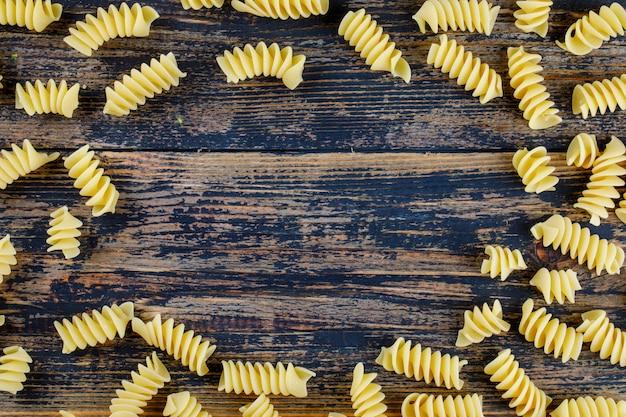 Maccheroni piatti laici su fondo di legno scuro. spazio di copia orizzontale per il testo