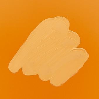 Macchia di fondotinta su sfondo arancione