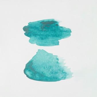 Macchie astratte acquamarina di vernici su carta bianca