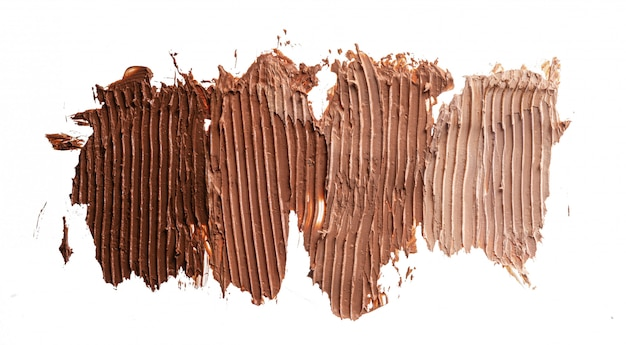 Macchie del fondamento cosmetico crema scuro isolate su bianco