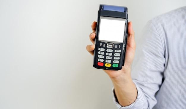 Macchina bancaria elettronica dello schermo bianco di manifestazione della mano dell'uomo d'affari alla ricezione, tecnologia del concetto senza contatto di pagamento