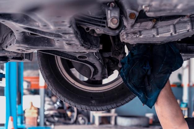 Macchina cambio olio meccanico. l'uomo sta cambiando l'olio del motore. sostituire l'olio del motore. sostituzione dell'olio dell'automobile. controllare il centro di servizio di riparazione di manutenzione auto.