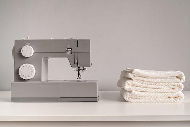 Macchina da cucire con asciugamani bianchi sul tavolo del sarto