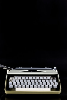 Macchina da scrivere sul tavolo su un muro nero. luogo di lavoro dello scrittore o dell'autore. bloger idea concept.