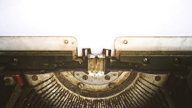 Macchina da scrivere vintage e un libro bianco vuoto, processo in stile vintage