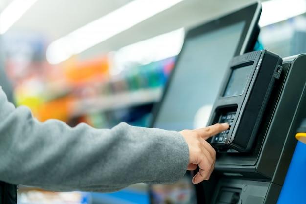 Macchina del cassiere del contatore di pagamento della mano del cliente del primo piano con il monitor nel deposito del supermercato