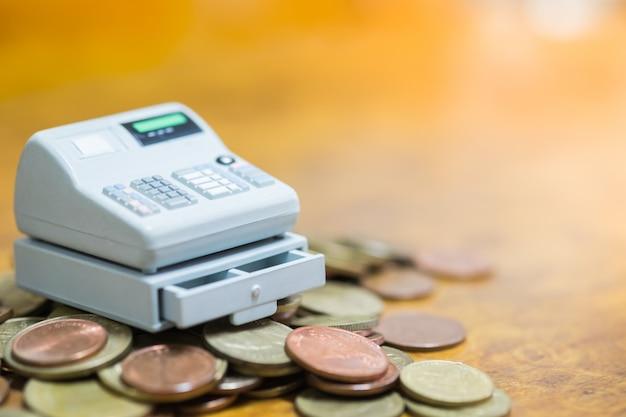 Macchina del cassiere di punto vendita in miniatura sul mucchio di monete