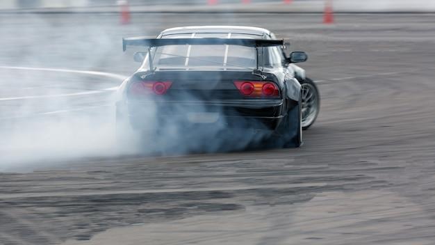 Macchina della sfuocatura di movimento che va alla deriva, automobile di spostamento dell'autista professionale sulla pista da corsa con il fumo.