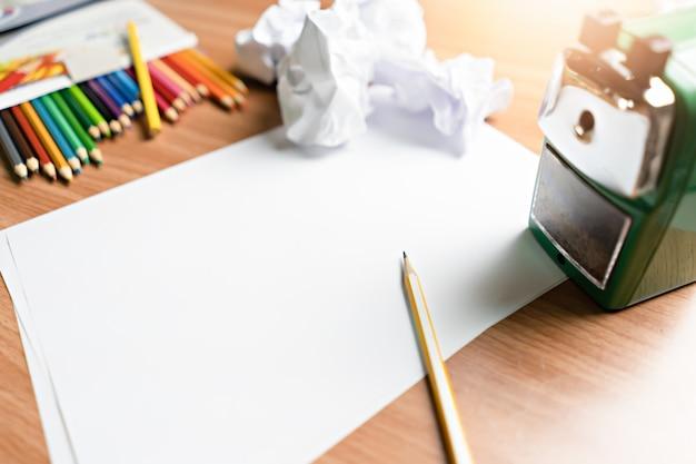 Macchina e carta di temperamatite con matite colorate sul tavolo