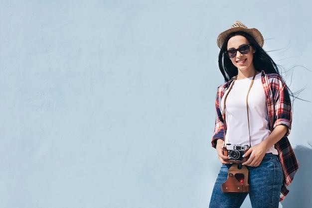 Macchina fotografica attraente sorridente della tenuta della donna che sta contro la parete blu