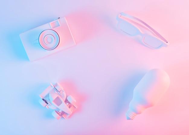 Macchina fotografica bianca dipinta; occhiali da vista; formula 1 auto e lampadina contro sfondo rosa