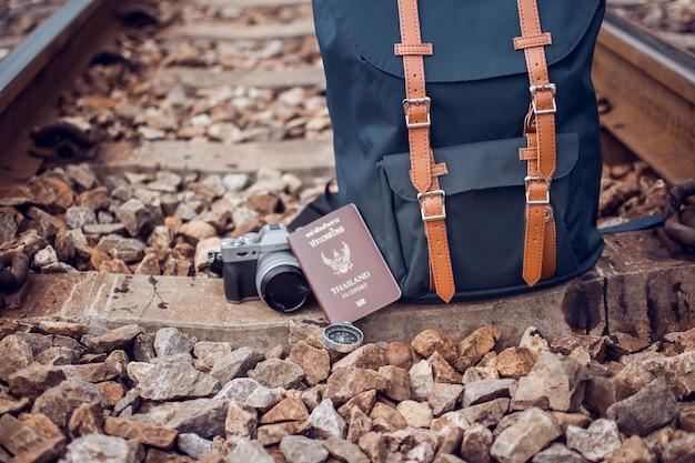 Macchina fotografica, bussola e borsa blu sulla ferrovia con tono vintage. il soggetto è sfocato.