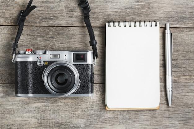 Macchina fotografica classica con la pagina in bianco del blocco note e la penna grigia sullo scrittorio di legno e d'annata grigio