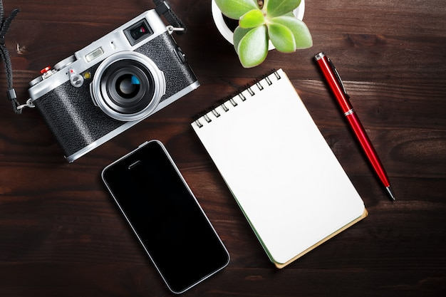 Macchina fotografica classica con la pagina in bianco del blocco note e penna rossa sulla tavola di legno di marrone scuro, tavola d'annata con il telefono e fiore verde