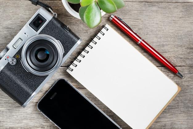 Macchina fotografica classica con la pagina in bianco del blocco note e penna rossa sullo scrittorio di legno e d'annata grigio con il telefono.