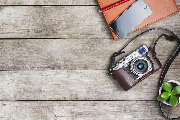 Macchina fotografica classica con una penna rossa dell'organizzatore marrone su una scrivania di legno grigia e d'annata con un telefono