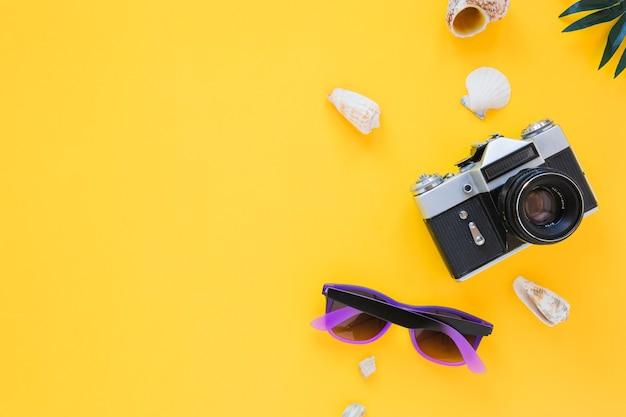 Macchina fotografica con occhiali da sole e conchiglie