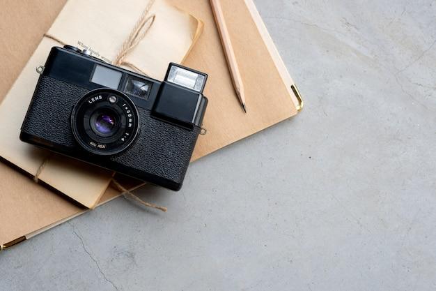 Macchina fotografica d'annata del primo piano e vecchio taccuino sul pavimento del cemento