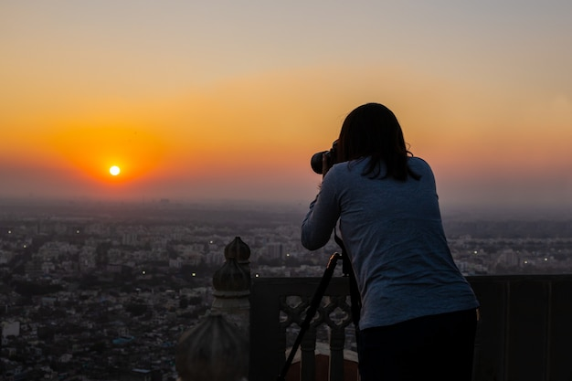Macchina fotografica del paesaggio della fucilazione della donna sul treppiede al tramonto in hahagarh fort jipur.