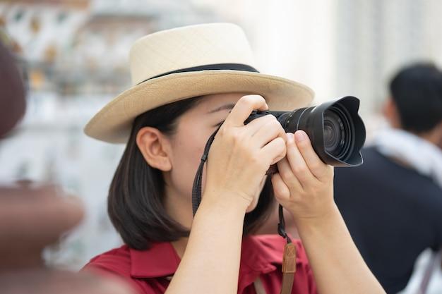 Macchina fotografica della stretta turistica bella donna per catturare i ricordi