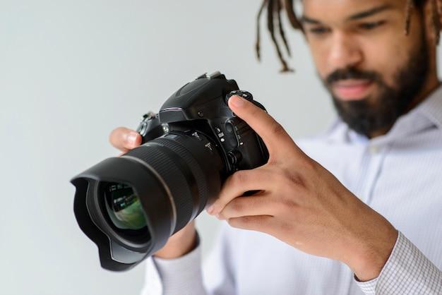 Macchina fotografica della tenuta del fotografo del primo piano