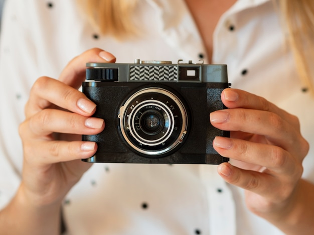Macchina fotografica della tenuta della donna di vista frontale
