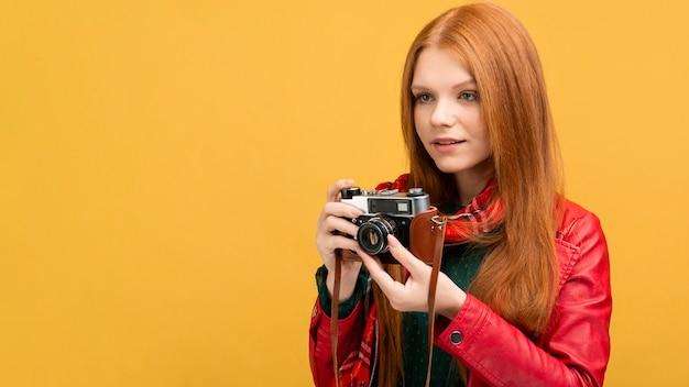 Macchina fotografica della tenuta della donna di vista laterale