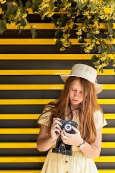 Macchina fotografica della tenuta della ragazza di vista frontale