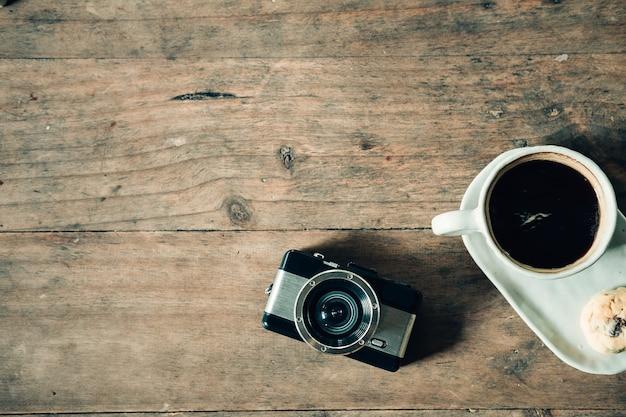 Macchina fotografica di restro e della tazza di caffè sulla tavola di legno con il tono d'annata
