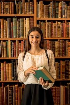 Macchina fotografica di sguardo femminile sorridente vicino allo scaffale per libri