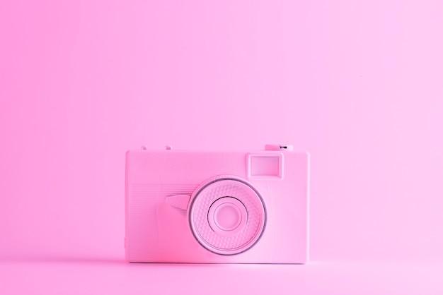 Macchina fotografica dipinta su sfondo rosa con copyspace per scrivere il testo