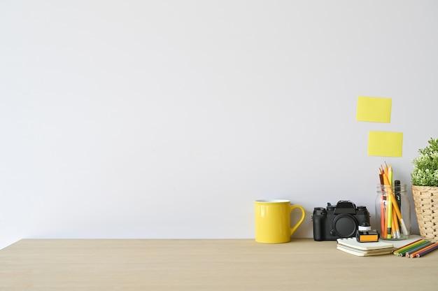 Macchina fotografica e articoli per ufficio creativi dell'area di lavoro sullo scrittorio di legno con lo spazio della copia.