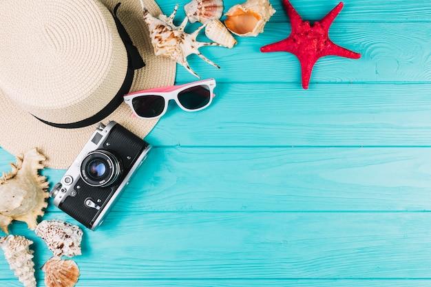 Macchina fotografica e cappello vicino a occhiali da sole e conchiglie