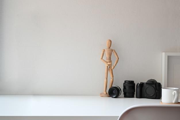 Macchina fotografica e lente con caffè sul tavolo e sulla sedia dello spazio della copia.