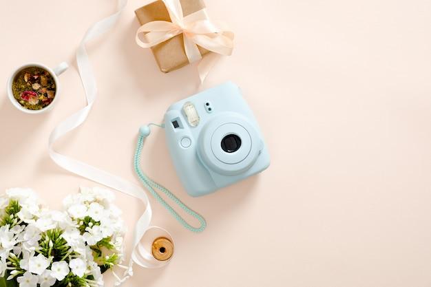 Macchina fotografica istantanea moderna, fiori margherita, tazza di tè, confezione regalo, nastro su sfondo rosa pastello