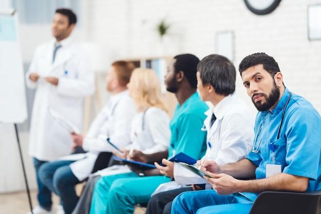 Macchina fotografica latina del medico che fissa durante la conferenza.