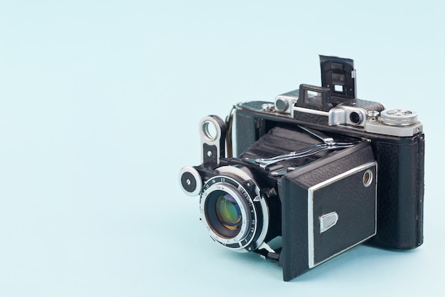 Macchina fotografica molto vecchia su uno sfondo blu delicato.
