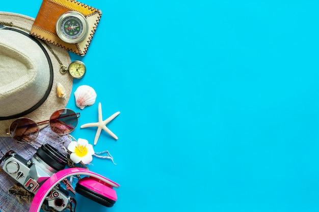 Macchina fotografica, occhiali da sole, bussola, cappello e cuffia su sfondo blu con spazio libero.