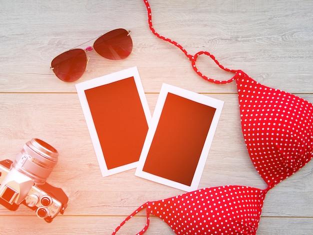 Macchina fotografica, occhiali, foto in bianco, costume da bagno su un fondo di legno.