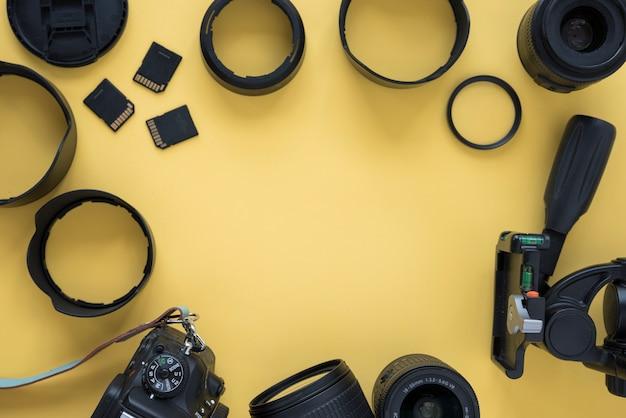 Macchina fotografica professionale moderna del dslr con gli accessori della macchina fotografica sopra fondo giallo
