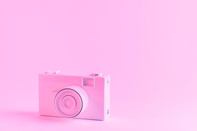 Macchina fotografica rosa dipinta contro fondo rosa